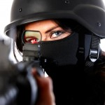 Northern Ireland stock photographer - woman wearing face mask and military style helmet looking through military rifle sight