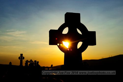 sun setting through a celtic cross in Ireland