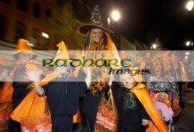 schoolchildren and teachers dressed as orange pumpkins parade down shipquay street Halloween Derry Ireland