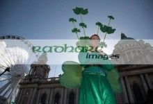 stiltwalker dressed in green wearing shamrocks at belfast city hall and big wheel before the parade and carnival on st patricks day belfast northern ireland