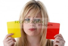 woman holding yellow and red cards