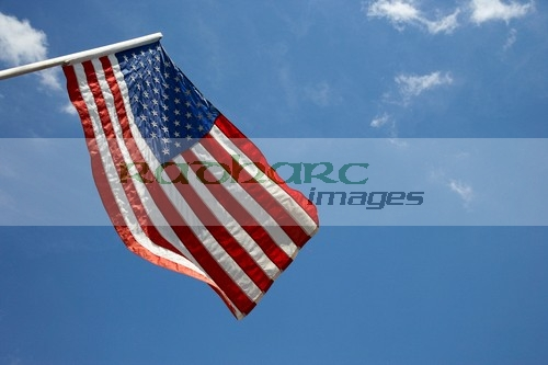 us american flag on flagpole against blue cloudy sky usa