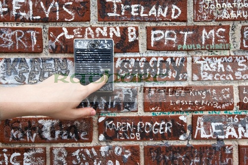 womans hand pushing old intercom button on wall covered in graffiti outside graceland memphis tennessee usa