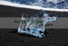 glacial iceberg fragment washed up on the black sand of jokulsarlon beach iceland