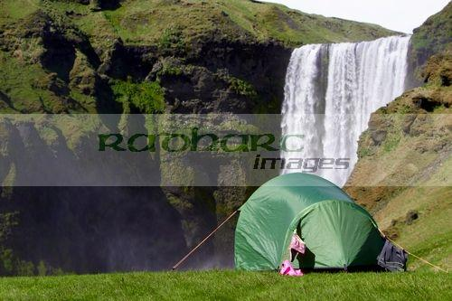small two person tent with clothes drying camping at skogafoss waterfall iceland